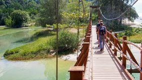 A group of tourists with backpacks goes on a suspension bridge. Across the river in summer stock image