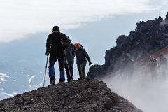 Group of tourists climbing to top crater of active volcano Royalty Free Stock Photography