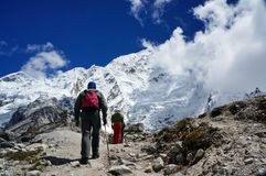 Group of tourists climbs the trail in the background of the snow-covered Himalayan mountains. LOBUCHE, NEPAL - September 17, 2014: Group of tourists climbs the stock photos