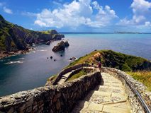 Group of tourists descending beautiful path of gaztelugatxe in Basque country, Spain. stock photos