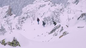 A group of tourists descends from the top of a snow-covered mountain. stock footage