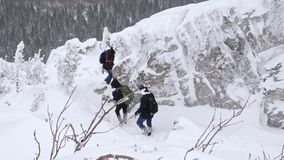 A group of tourists descends from the top of a snow-covered mountain. stock video footage