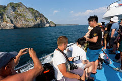Group of tourists on ferry boat going to tropical island with cliffs and clear water Royalty Free Stock Photo