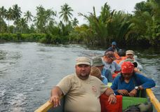 The group of tourists floats on a wooden canoe down the river. Royalty Free Stock Photo