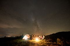Group of tourists with guitar by burning bonfire under dark starry sky with Milky Way constellation. Company of five happy tourists hikers with guitar, men and stock photography