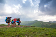 Group of tourists hikers with backpacks standing in mountains  Royalty Free Stock Photos