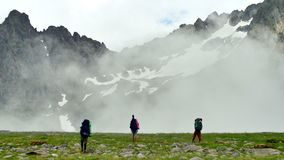 Group of tourists with Hiking backpacks coming in High Snowy Mountains with Clouds in Kavkaz region stock footage