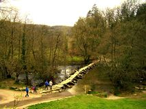 A group of tourists hiking, cross the ancient Tarr Steps Bridge. royalty free stock photography