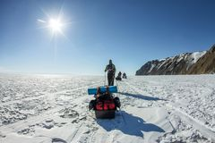 Group of tourists with ice sleds walking along the ice of Lake Baikal Royalty Free Stock Image