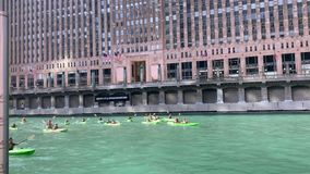 Group of tourists in kayaks converge on the Chicago River as they paddle away from the Merchandise Mart. On a gorgeous summer afternoon stock video footage