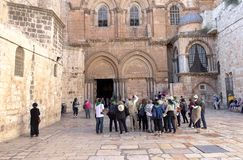 Group of tourists listening to the guide at the entrance of the Church of The Holy Sepulcher. royalty free stock image
