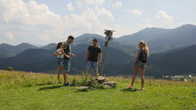 A group of tourists looking for a road in the mountains with a pointer and phone.  stock footage