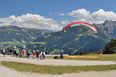 Group of tourists looking to paraglider starting to fly. Royalty Free Stock Image