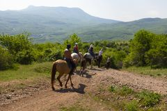Group of tourists on the mountain equestrian trip on horses around the Ghost valley stock image