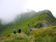 A Group Of Tourists On A Mountain Ridge. Mist covering the peak royalty free stock photography