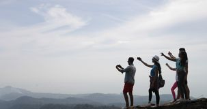 Group Of Tourists On Mountain Top, People Enjoy Landscape With Sunrise Taking Photos On Cell Smart Phone. Slow Motion 60 stock video footage