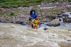 A group of tourists passes a rough mountain river for a wade. A group of tourists with large backpacks passes a rough mountain river for a wade.In the royalty free stock image