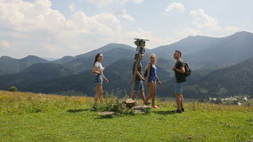 A group of tourists passes by a signpost in the mountains.  stock video footage