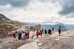Group Of Tourists People On Top Of Norwegian Mountains Trolltung Stock Photo