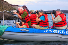 Group of tourists photographing from a dinghy near Bartolome isl Royalty Free Stock Photo