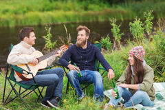 Group of tourists playing guitar in camping Royalty Free Stock Image