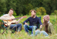 Group of tourists playing guitar in camping Stock Photography