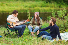 Group of tourists playing guitar in camping Royalty Free Stock Photos