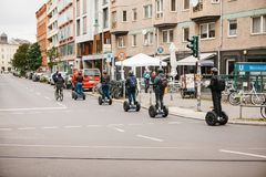 Berlin, October 3, 2017: Group of tourists riding on gyroscooters along the streets of Berlin during excursion. Group of tourists riding on gyroscooters along Stock Photos