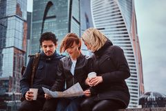 Group of tourists searching place on the map while sitting with takeaway coffee in front of skyscrapers. In Moscow city royalty free stock image