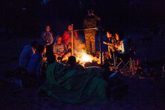A group of tourists sitting around the campfire at night. Stock Photo