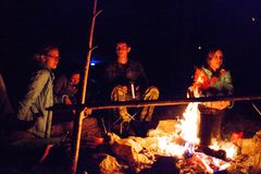 A group of tourists sitting around the campfire at night. Royalty Free Stock Images