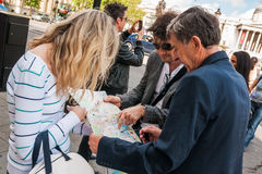 Group of tourists standing at Trafalgar Square and looking at map Stock Photo