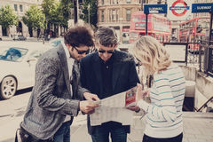 Group of tourists standing at Trafalgar Square and looking at map Royalty Free Stock Photography