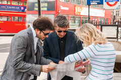 Group of tourists standing at Trafalgar Square and looking at map Stock Photos