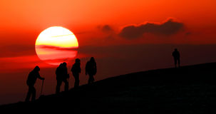 Group of tourists take to the mountains at sunset. Silhouette Royalty Free Stock Images