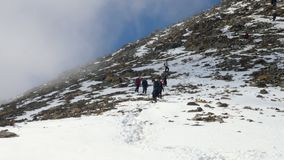 Group of tourists team returns from a difficult trek to the mountains in winter