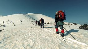 A group of tourists travels through the snow-capped mountains. A group of travelers through the snow-capped mountains stock video
