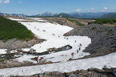 Group of tourists traverse mountain river on snowfield. Kamchatka, Far East, Russia Stock Photo
