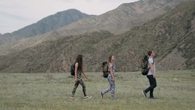 A group of tourists walk along a trail in the mountains in summer weather. A group of tourists with backpacks walk along a trail in the mountains in summer stock video