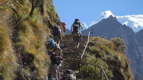 A group of tourists walking along the high-mountain trail in the Himalayas. NAMCHE, NEPAL - OKTOBER 22, 2017: A group of tourists climbs a steep trail in the stock video footage