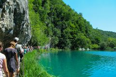 A group of tourists walking along a narrow path next to the insanely beautiful blue lake. royalty free stock photography