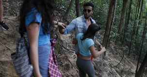 Group Of Tourists Walking Down Hill In Forest Trekking, People On Hike Friends Hikers Helping Each Other. Slow Motion 60 stock video footage