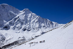 A group of tourists walking on the snow slope Royalty Free Stock Photo