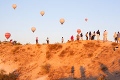 Group of tourists watching balloon fly on top of mountain Stock Photo