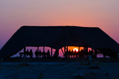 Group of tourists watching colorful sunset under shelter. Tourist resort in Africa. Backlight, silhouette, rear view, unrecognizab Royalty Free Stock Images