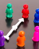 Group of toy peoples and white arrow Stock Images