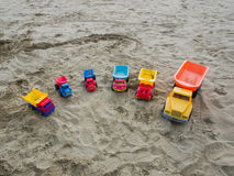 Group of toy working trucks on a sandy beach Stock Photo