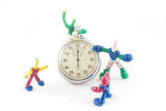 Group of toys, playing with a clock. Funny group of  toys,  playing with a clock, isolated on white Royalty Free Stock Photo