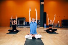 Group with trainer sitting in yoga pose Royalty Free Stock Photos