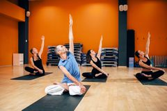 Group with trainer sitting in yoga pose. Relaxation, female group with trainer sitting in yoga pose, workout in gym. Yogi indoor Stock Photography